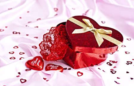 Rosa ropa de cama, regalo cuadro en forma de coraz�n chocolate candy con las palabras I Love You y un mont�n de peque�os corazones distribuidos. Sorprende a la mujer. Foto de archivo - 8575384