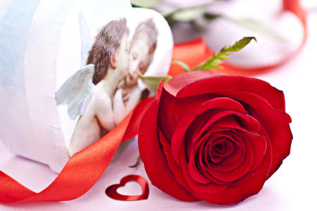 Beautiful red rose with gift box shaped as heart with angels and small red shaped heart. Stock Photo - 8646033