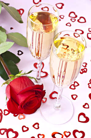 image date: Beautifull red rose with two glasses of champagne on the pink surface with red hearts.