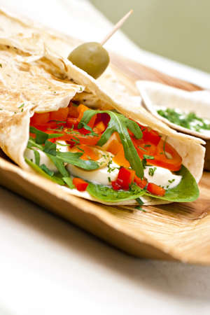 wheat wrap with olive filled with tomato, mozarello, bell pepper and salad. Some dip.