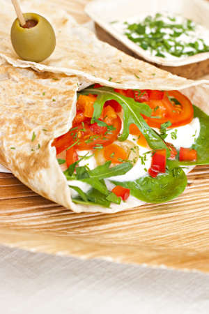 wheat wrap with olive filled with tomato, mozarello, bell pepper and salad. Some dip. photo