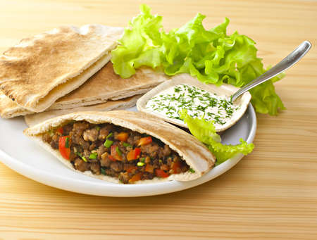 Pita bread with grilled meat and fresh salad. photo
