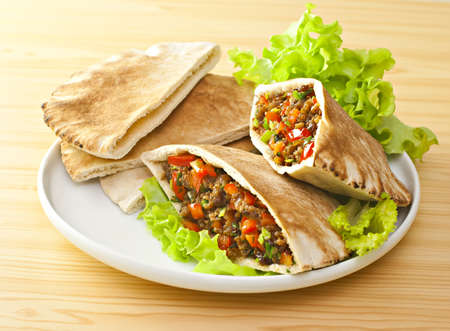 Pita bread with grilled meat and fresh salad.