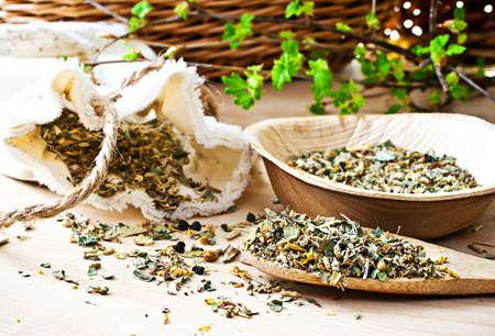 homeopatia: Bolsas con t� verde, cuchara de madera, ramas con nuevos brotes.