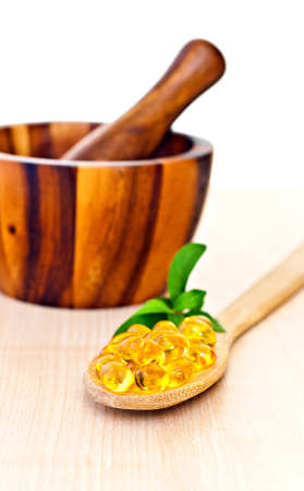 Fish oil a wooden spoon, mortar with a pestle. photo