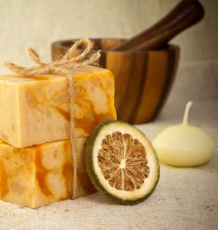 Natural soap with a dry lemon mortar with a pestle and a candle. Health spa for spa treatment. photo
