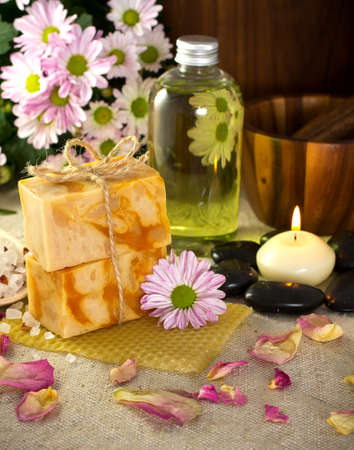 Natural soap from honey. Olive oil, massage stones with a candle, mortar with a pestle. Health spa for spa treatment. photo