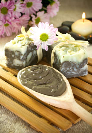 Spa treatment. Clay, burning candle, natural soaps, flowers. photo