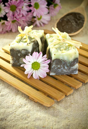 natural soap: Natural soap, handmade. Pink flowers and spoon with cosmetic clay.
