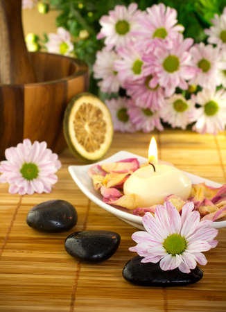 Spa treatment.Burning candle,  spa stones, dry lemon, pink flowers.