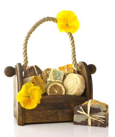 grooming product: Composition of the basket full of handmade soap, isolated on white background. Stock Photo