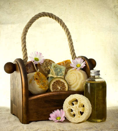 Composition of the basket full of handmade soap with bottle of oil and some flower decoration.