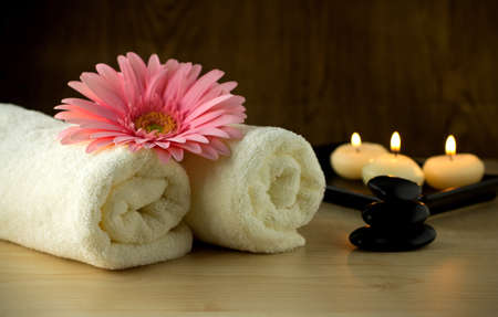 Towels and pink flower, candles and massage Stones in a Zen Spa.