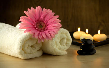 Towels and pink flower, candles and massage Stones in a Zen Spa. photo