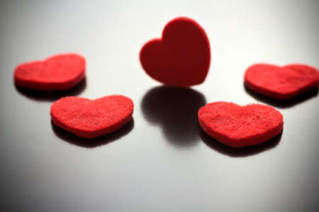 Five red hearts on a gray background. photo