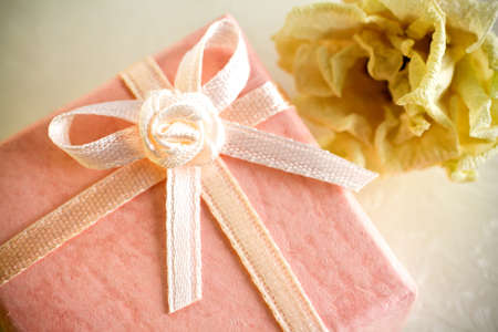 Pink gift box with a dry rose. photo