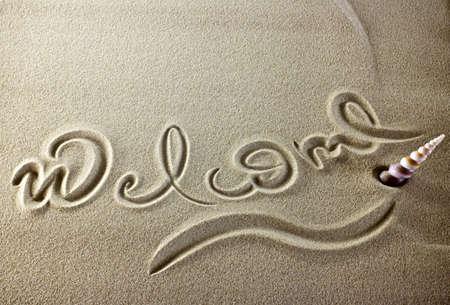 bienvenidos: Simple mensaje de bienvenida en la arena con una concha. Foto de archivo