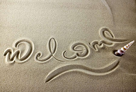 Simple welcome message in the sand with a shell.