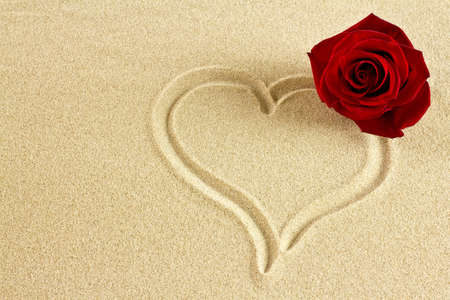 On the sand drawn on the heart and red rose. photo