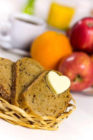 Slices of bread in the basket of butter in a heart   A healthy breakfast  Coffee, juice and fresh fruit  photo