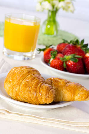 Tasty breakfast  Croissants with juice, and fresh  strawberries  photo
