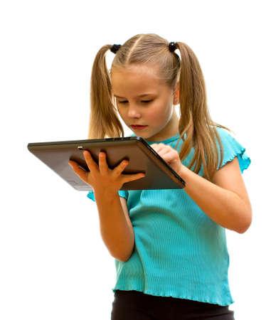Jeune fille debout, tenant, et en regardant dispositif de tablette PC.