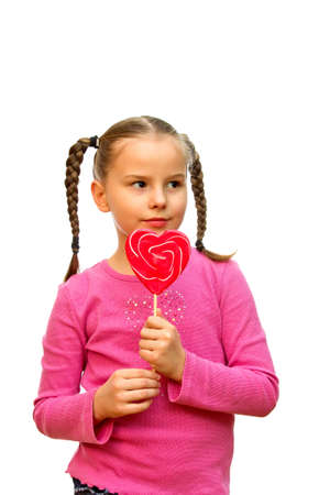 sucking lollipop: A young girl holds the lollipop in the form of heart, isolted on a white background  Stock Photo