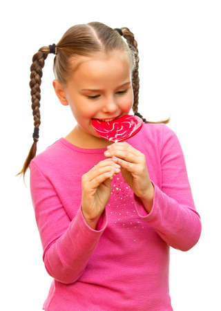 A young girl eating lollipop heart-shaped  photo