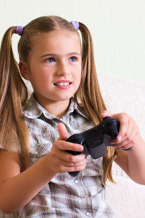 A teenaged girl playing video, computer  game. photo