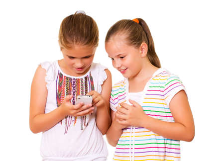 Two girls play with the iPhone  Isolated on the white background  photo