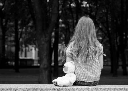bambini tristi: Giovane ragazza seduta in un parco e nero fotografia in bianco
