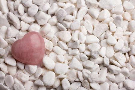 Rose quartz heart on pebbles. Stock Photo