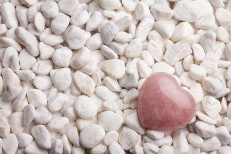 love image: Rose quartz heart on pebbles. Stock Photo