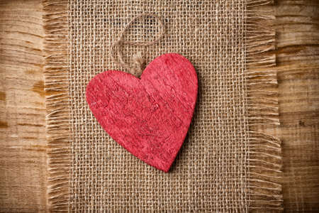 love image: Red wooden heart on a linen cloth and wood background