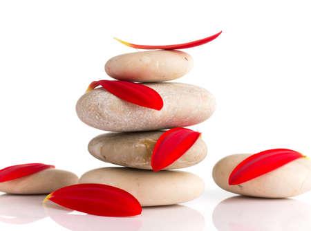 Spa Steine ??und rote gerber Blütenblätter auf dem weißen Hintergrund isoliert