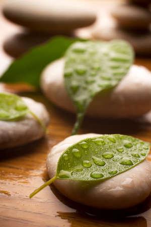Massage stenen met groene bladeren en water druppels. Hout achtergrond. Stockfoto