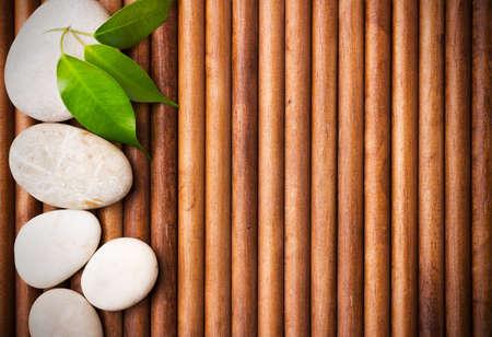 Massage pierres avec des feuilles vertes, fond bois.