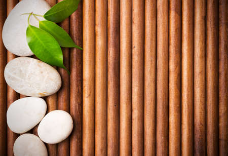 Massage stones with green leaves, wood background. Stockfoto