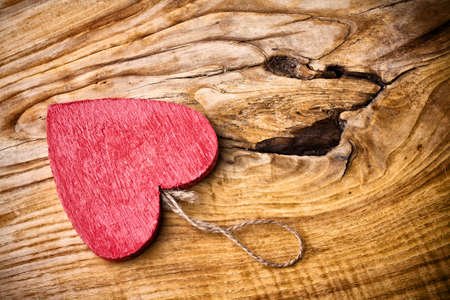 On wooden background red wooden heart. photo
