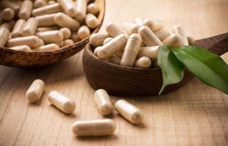 Alternatieve geneeskunde tabletten op een houten lepel, groene blad.