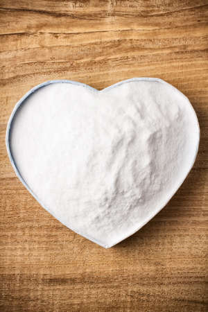 sodium bicarbonate: Soda, heart-shaped box. Wooden surface.