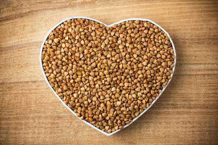 Buckwheat, heart-shaped box  Wooden surface  Stockfoto