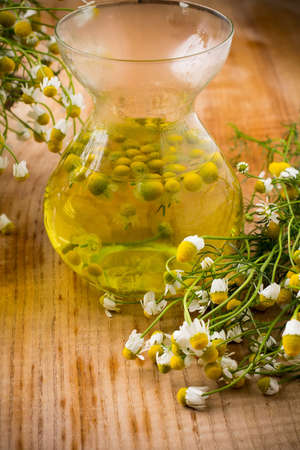 Chamomile flowers on a wooden surface. Chamomile aromatherapy, oil. Stockfoto