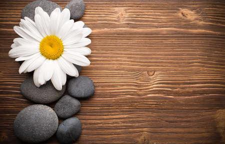 Evenwichtige spa stenen met kamille bloem en houten achtergrond.