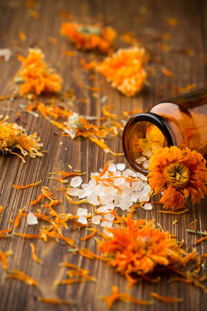 Homeopathic medicine, calendula dry flowers and wooden surface.