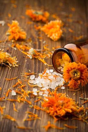 Homeopathische geneeskunde, calendula droge bloemen en houten oppervlak. Stockfoto