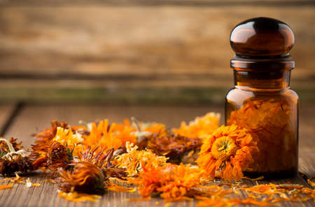 Homeopathic medicine, calendula dry flowers and wooden surface  photo
