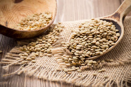 Lentils wooden spoon on wooden background. Healthy food. photo