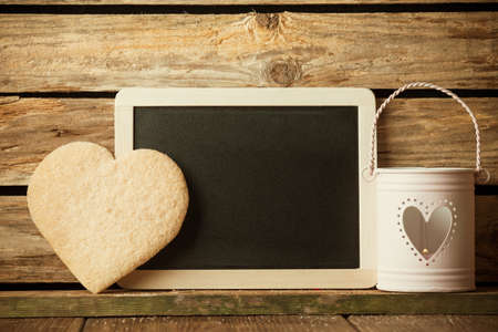 Heart of the cookies and blackboard,  wooden background. photo