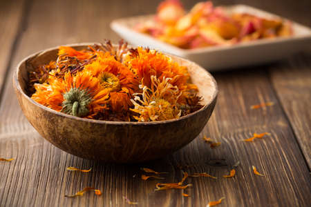 Homeopathic medicine, calendula dry flowers and wooden surface